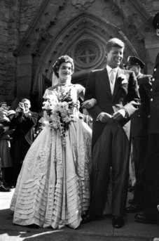 Jacqueline Bouvier in gorgeous Battenburg wedding dress with her husband Sen. John Kennedy as they stand in front of church after wedding ceremony