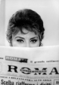 Sophia Loren impishly peering over the top of a newspaper