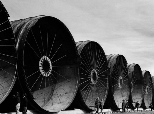 Workmen stand beside gigantic pipe segments during construction of Montana's Fort Peck Dam in 1936