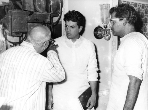 This photograph almost gives the impression that David is directing Dharmendra, while the real director passively looks on