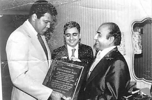 Muhammad Ali hands over a plaque to Mohammed Rafi